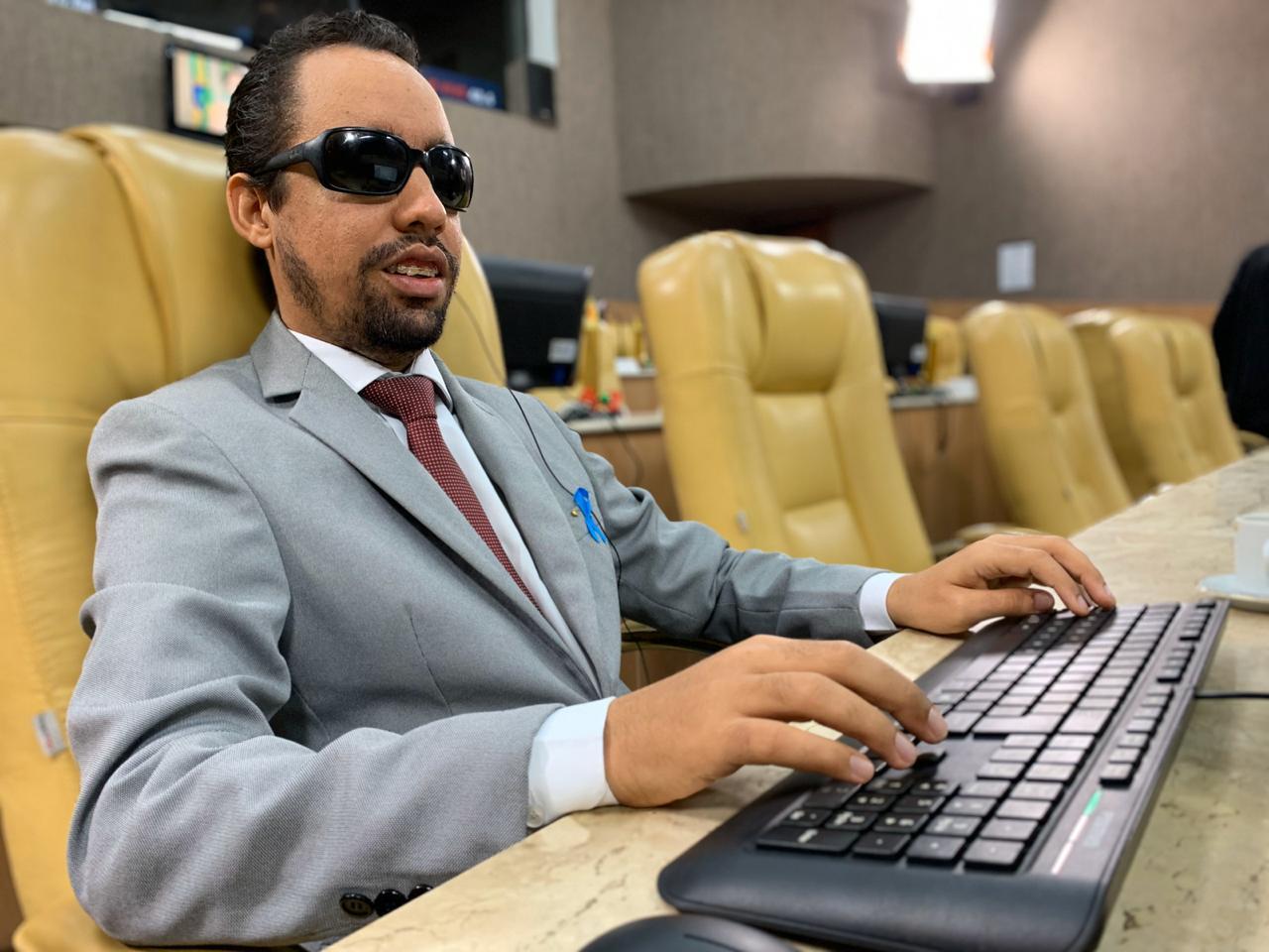 #PraTodoMundoVer Lucas sentado no plenário da Câmara com as mãos sobre o teclado do computador