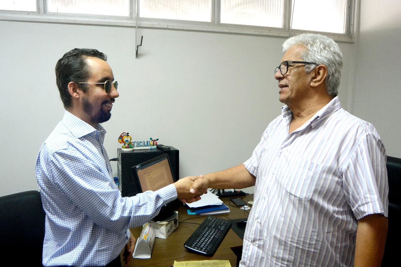 #PraTodoMundoVer Lucas está em pé apertando a mão de Eugênio Nascimento, também em pé. Eles sorriem um para o outro. (Foto: André Moreira)