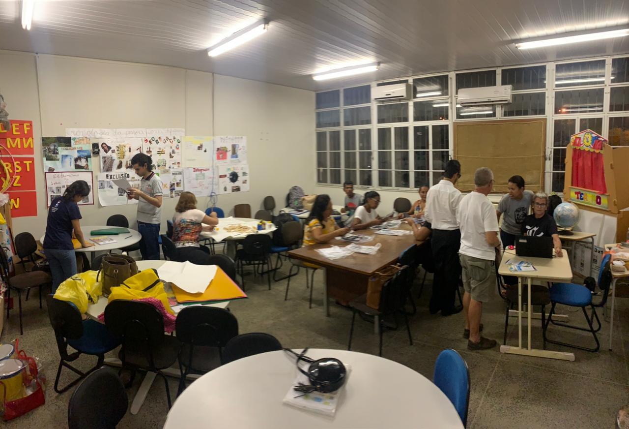 #PraTodoMundoVer Foto Panorâmica de uma sala de aula com mesas, cadeiras e pessoas sentadas e em pé