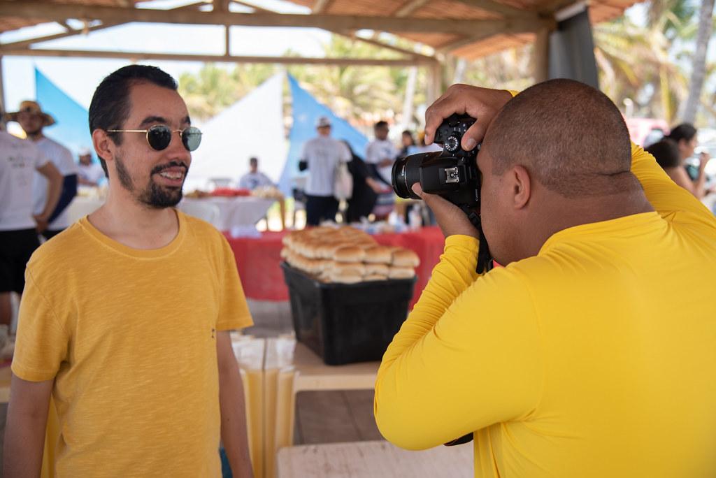 #PraTodoMundoVer Fotografia horizontal, Lucas Aribé posa para registro fotográfico que é feito por um garoto que está à sua frente segurando uma câmera
