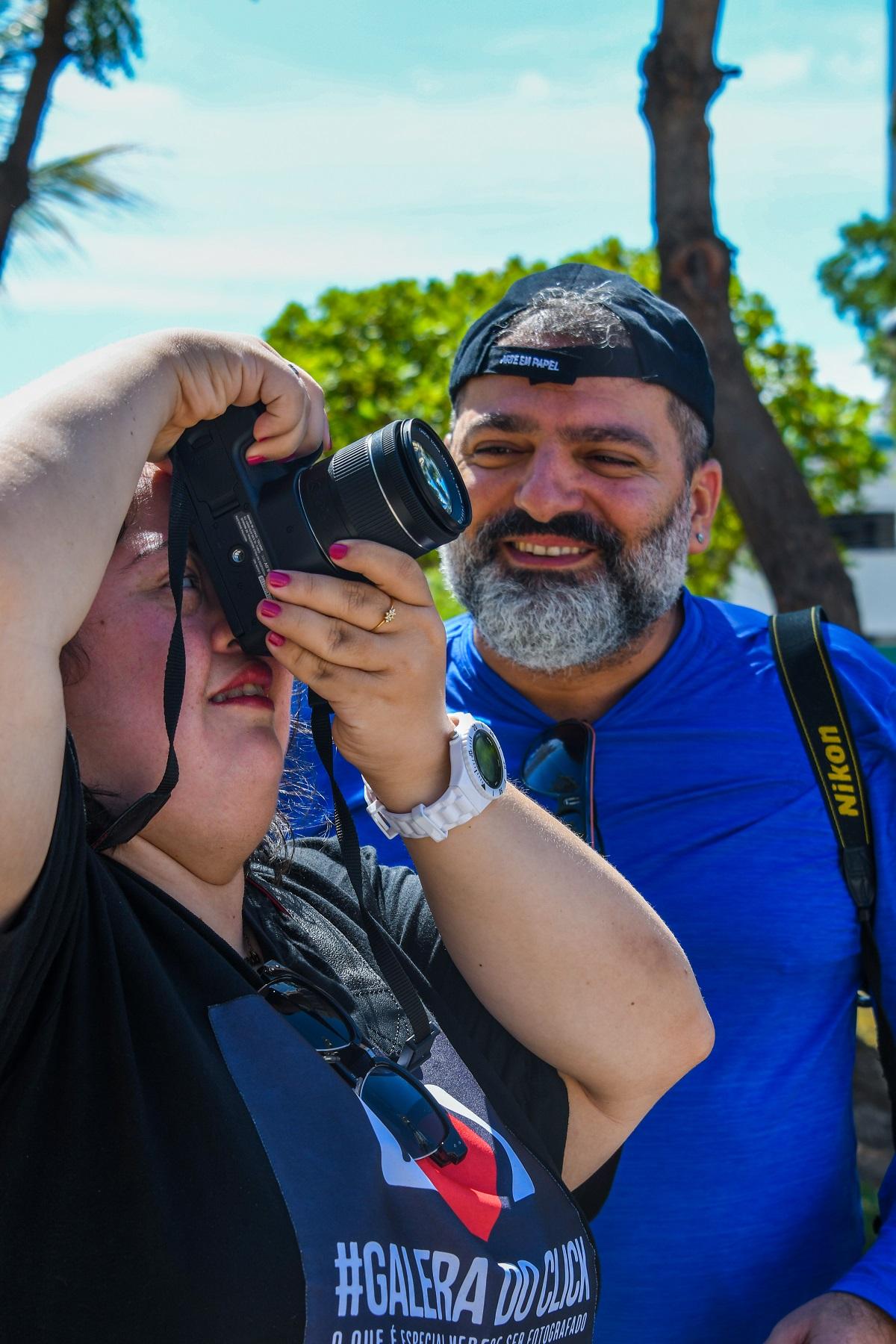 #PraTodoMundoVer Em primeiro plano uma jovem com down segura uma câmera fotográfica na altura do rosto. Em segundo plano, um homem vestindo camisa azul e boné olha para a garota sorrindo